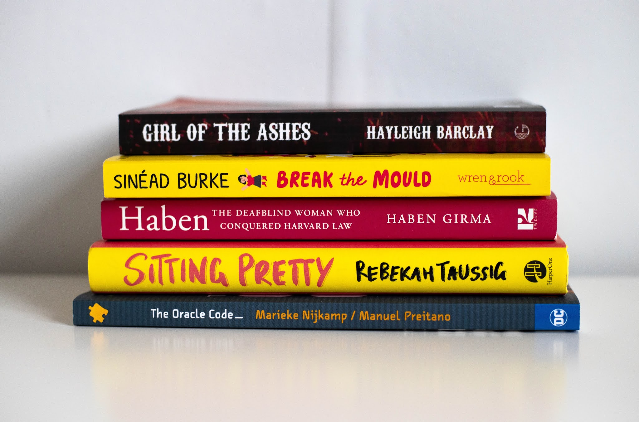 5 books are stacked on top of eachother against a white background. Top to bottom they are: Girl of the ashes by Hayleigh Barclay, Break the mould by Sinead Burke, Haben the deafblind woman who conquered Harvard law, Sitting pretty by Rebekah Taussig and The Oracle code by Marieke Nijkamp and illustrated by Manuel Preitano.