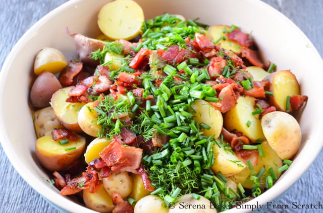 Warm sliced red potatoes, cooked crispy bacon, fresh dill and chopped chives in a large bowl.