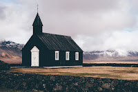A black simple church with scenery behind it