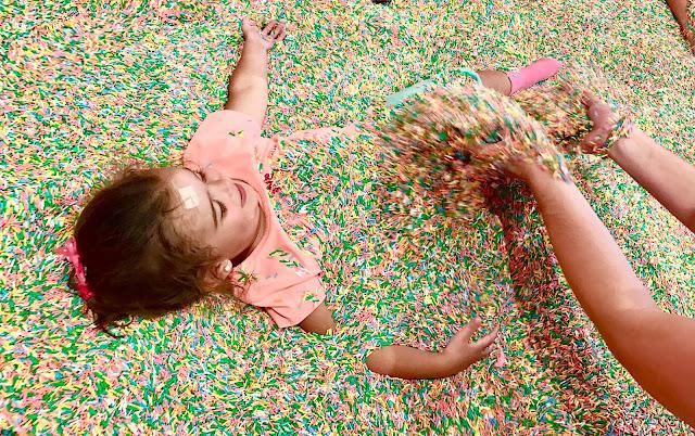 Toddler being buried in colorful sprinkles