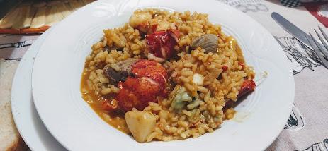 Plato con arroz caldoso de bogavante, sepia y almejas