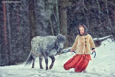 Poni y niña en la nieve