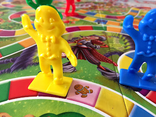 A game of Candy Land in play, with happy gingerbread characters on a colourful trail