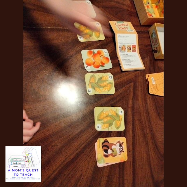 Clumsy Thief Junior game cards and game in action with A Mom's Quest to Teach logo