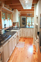 Laminate wooden floor for narrow kitchen ideas with black countertops and white cabinets