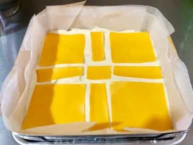 Cara Menyusun Lapisan Lembaran Keju Cheddar Pada Kue Pillow Cake