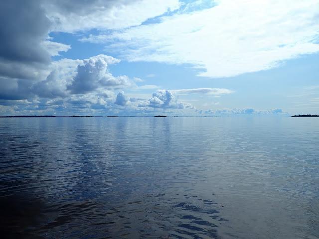 Tyyni meri, taivaalla kumpupilviä.