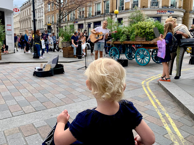 Child dancing while watching a busker play guitar and sing