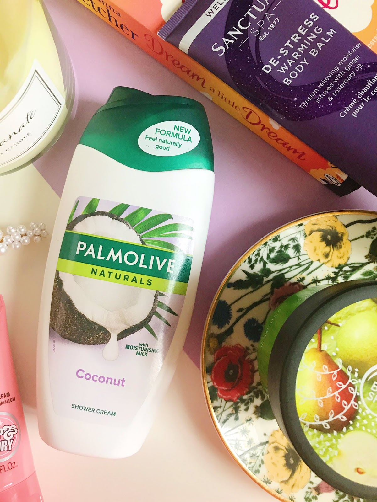 Palmolive Coconut Shower Cream surrounded by various other beauty products, books and candle