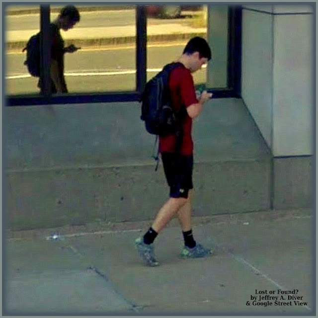 Man in red shirt, shorts, dark socks & sneakers on phone