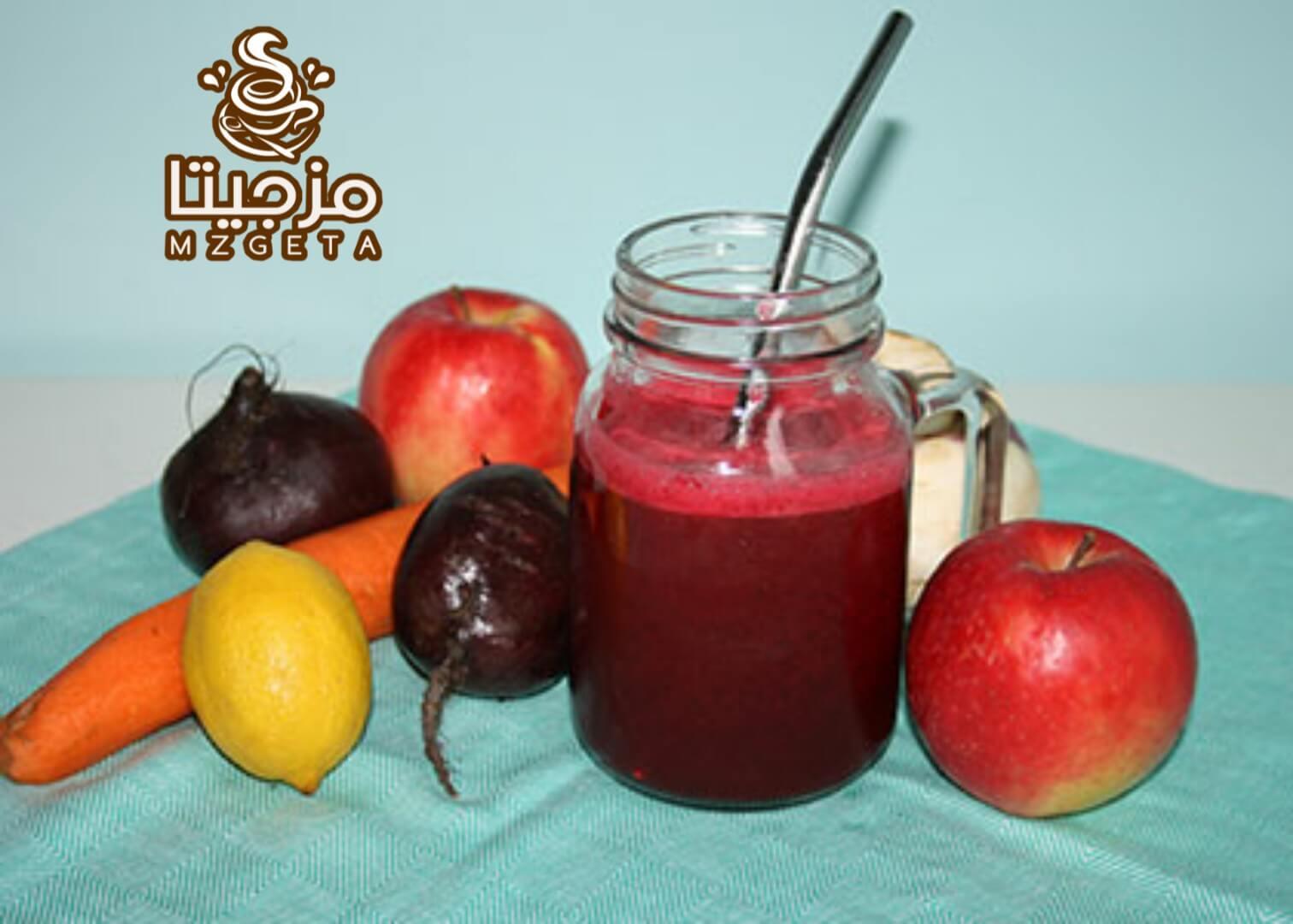 برطمان من عصير الرمان بالبنطر وبجواره بعض الفواكه تفاح وشمندر وجزر وليمون