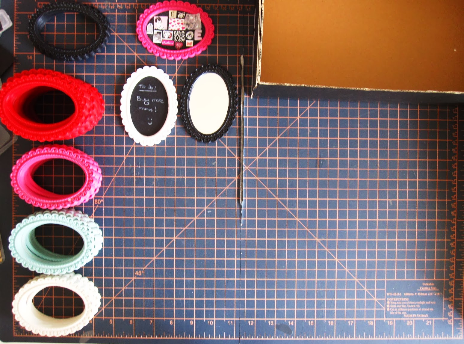 Stacks of various coloured rubber miniature baroque-style frames on a cutting mat