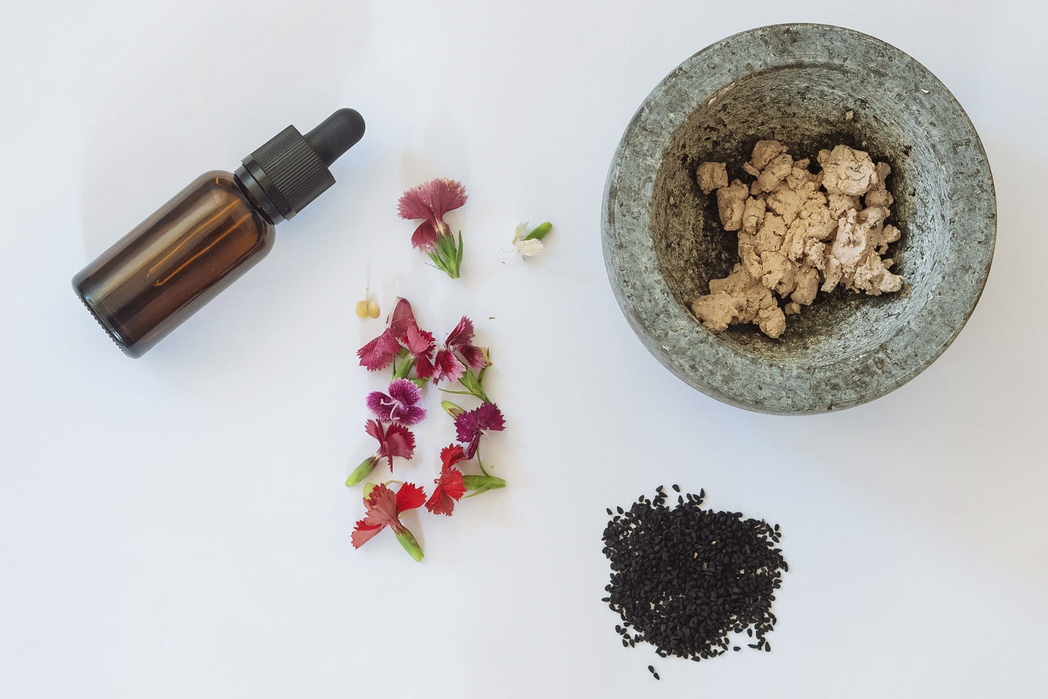 few skincare ingredients and a dropper bottle on a plain background