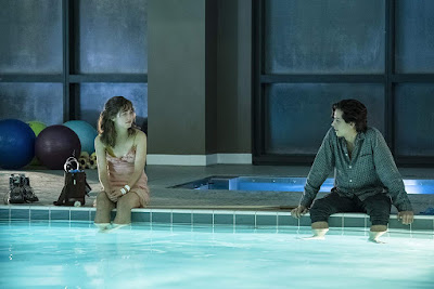 Will (Cole Sprouse) and Stella (Haley Lu Richardson) sit near each other with their feet in a pool as they talk about love and cystic fibrosis in the movie Five Feet Apart