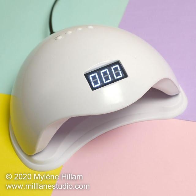36 watt nail lamp on a pastel green, purple, pink and yellow background