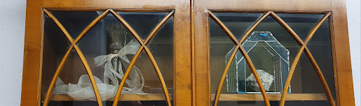 A wooden cabinet with glass doors. Inside, a tarnished silver vase and ribbons, and a stained glass sculpture.