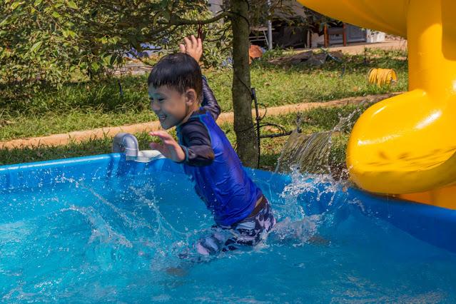 Bé thỏa sức vui đùa trong hồ bơi giữa vườn sầu riêng