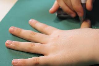 Criança a fazer o contorno da mão em folha eva