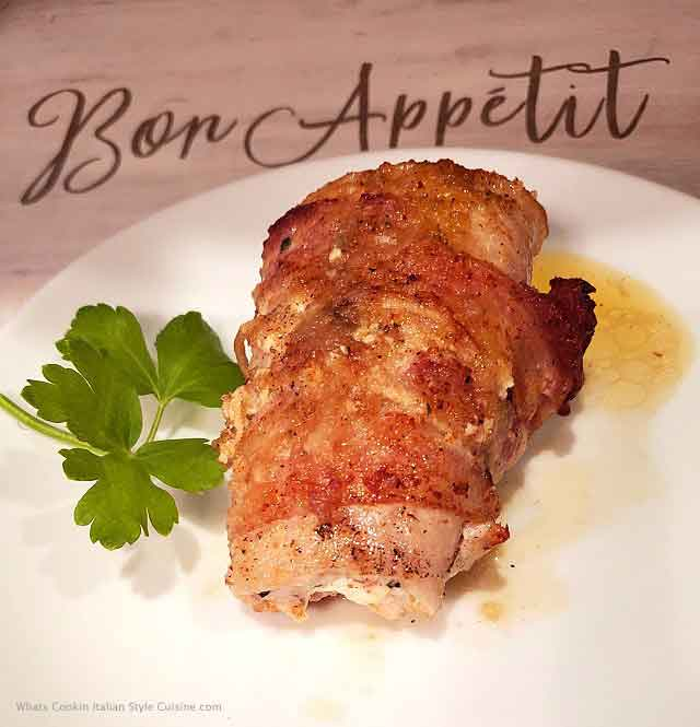 this is pork tenderloin stuffed with ham and cream cheese rolled up and baked on a white plate with parsley