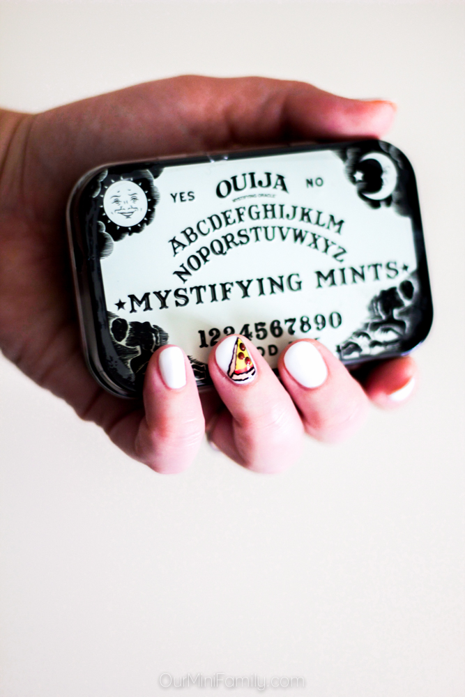 Hand Holding a Ouija Board Mints Box with Pizza Nails