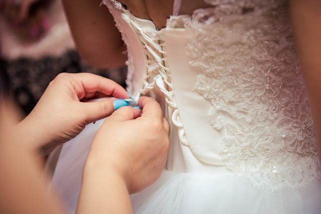 Image of bride putting on and lacing up her wedding dress on her wedding day.