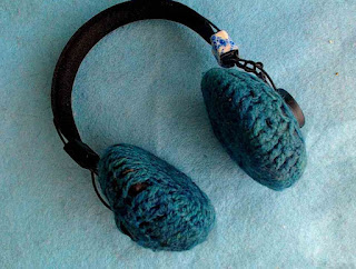 a pair of headphones with crochet covers on the earpieces and a small band of blue-and-white washi tape on the headband.