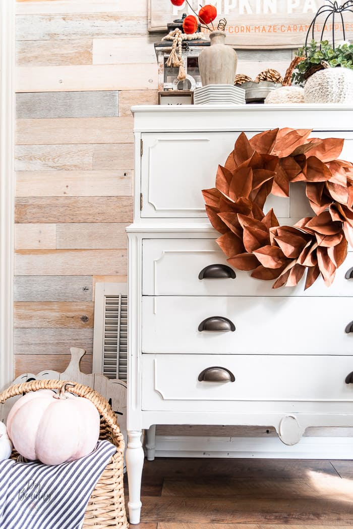 copper wreath hung on white dresser with Fall decor and pumpkins and wood wall