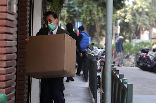 Man in green mask delivering large box