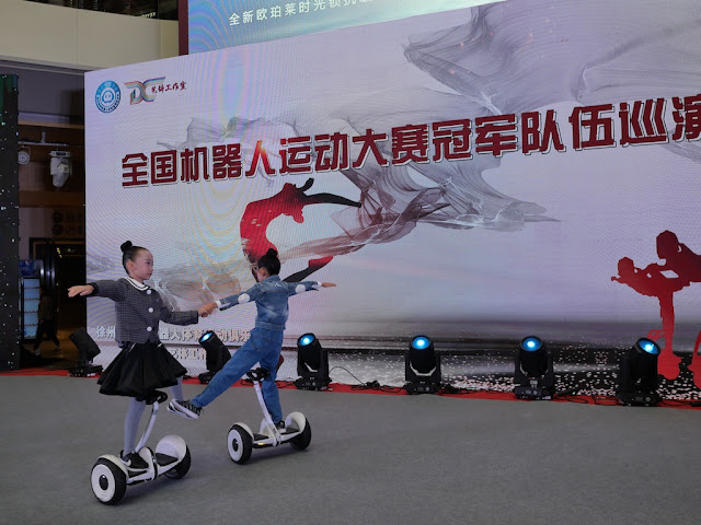 two girls dancing while on self-balancing scooters
