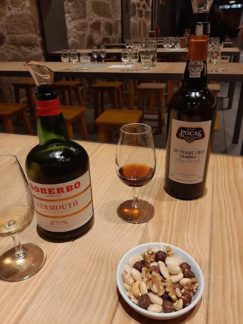 Garrafas de vermute Soberbo de vinho do Porto Poças, copo com vinho do Porto e prato de frutos secos