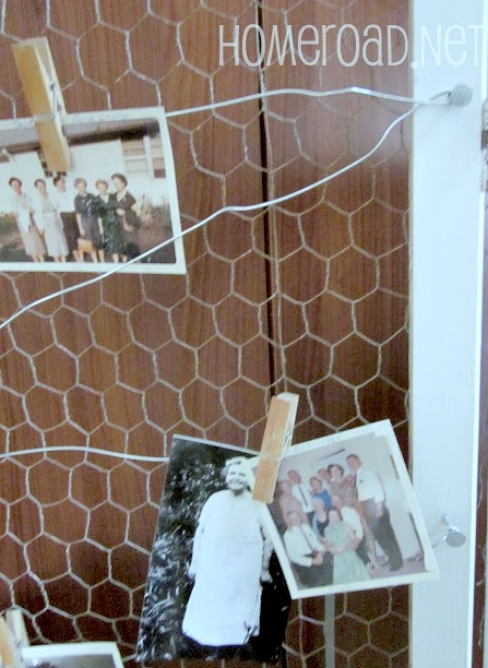 Chicken wire with photos hanging on wire.