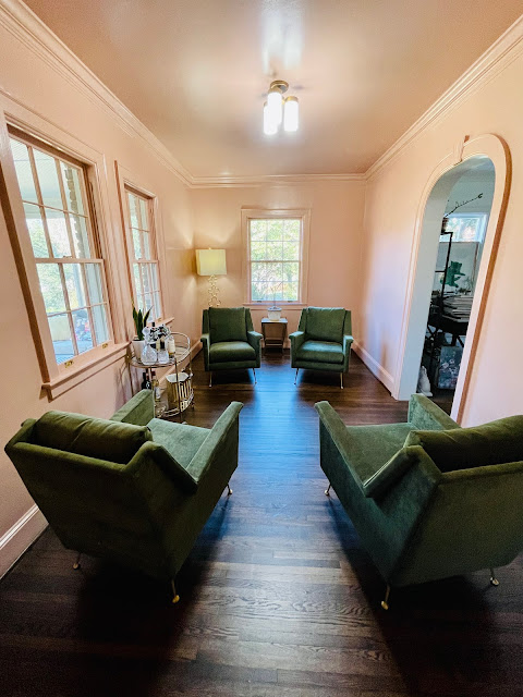 small pink room with four green arm chairs