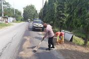 Cegah Kecelakaan, Polisi Polsek Kemangkon Bersihkan Tumpahan Solar di Jalan