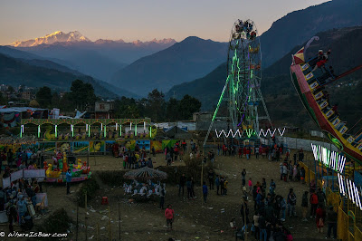 local festivities in Besisahar, ferris wheel with mountains in the background, snow himalayas, nepal WhereIsBaer.com Chris Baer