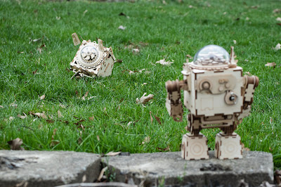 A wooden robot standing on a stone watching a wooden dog looking at a stick on the grass.