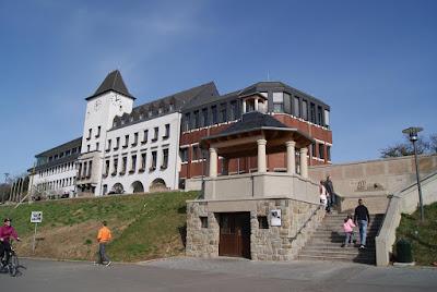Man sieht einen Bahnhofsartigen Bau in weißer Farbe mit einem Turm und einem braunen Anbau. Der Turm hat an zwei Seiten eine große Uhr,