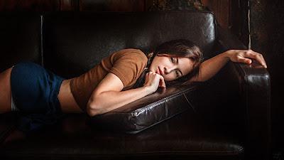 Linda chica acostada en sofá de cuero mirando a cámara