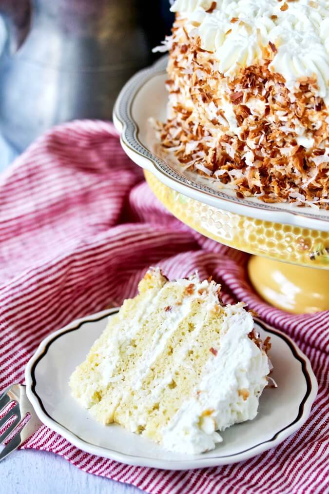 Italian Coconut Crème Cake with toasted coconut and piped cream