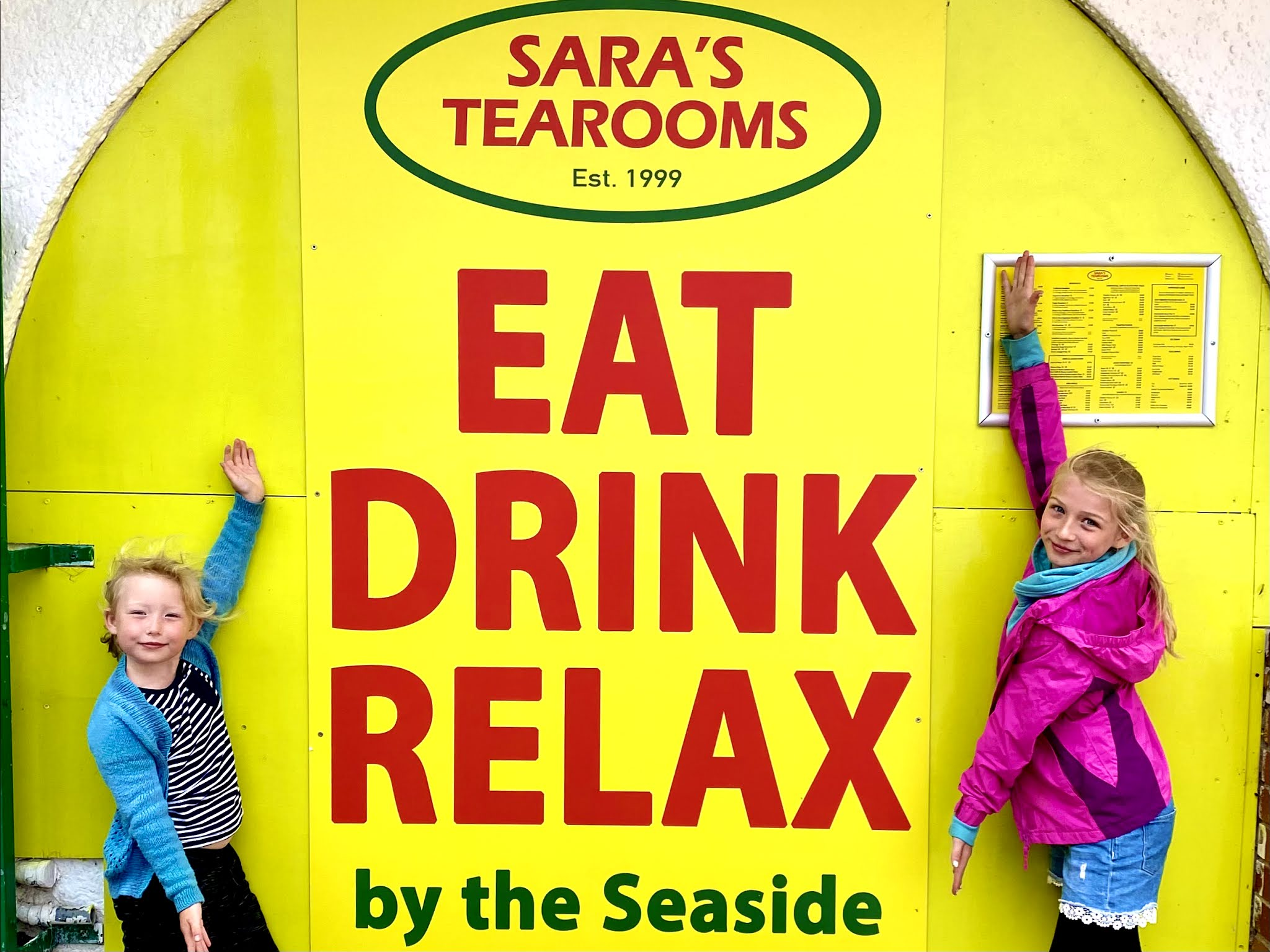 Two children posing by a bright yellow sign advertising Sara's Tearooms on Great Yarmouth Beachfront