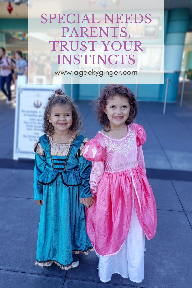 Two little girls standing in front of Hollywood Studios, the one on the left wearing a teal colored dress and the one on the right wearing a pink and white dress.