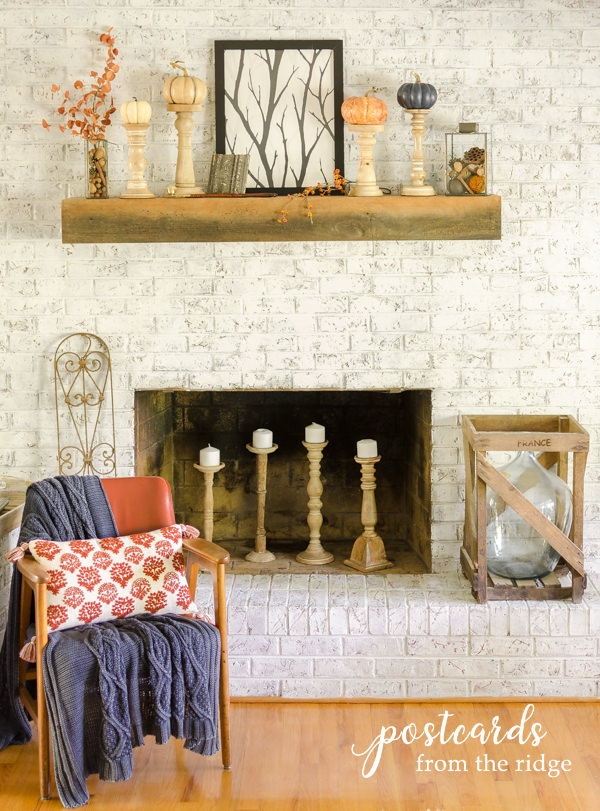 white painted brick fireplace with wood beam mantel and fall decor