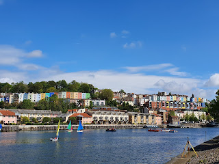 Photo of Bristol harbour in the sun with sailing boats on the water and colourful houses overlooking