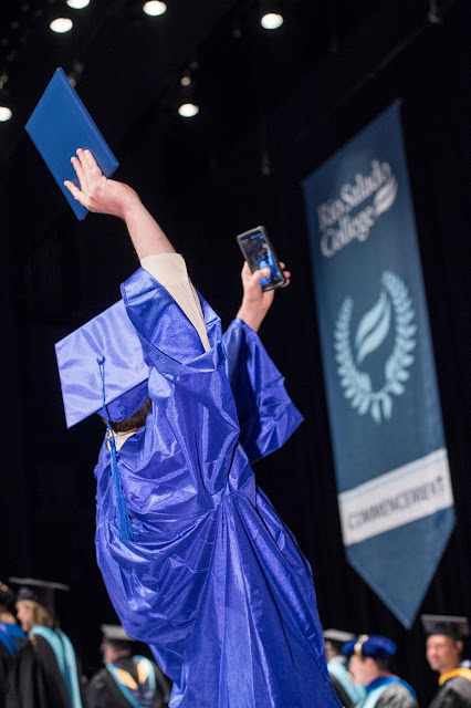 Image of a student taking a selfie at graduation 2017, dressed in cap and gown, in front of commencement banner and stage.