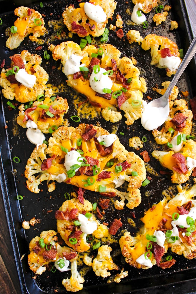 Top view of loaded cauliflower steaks on a sheetpan.