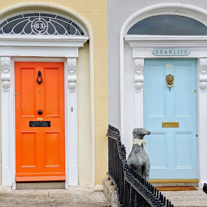 Orange and pale blue Dublin doors with dog statue on Sandymount Strand