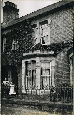 Lady and 2 children outside house