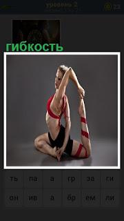 На полу девушка демонстрирует свою гибкость, подняв ногу к голове