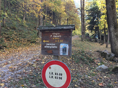 Sign at the start of the hike near Pian delle Gorre marking the time to reach Garelli.