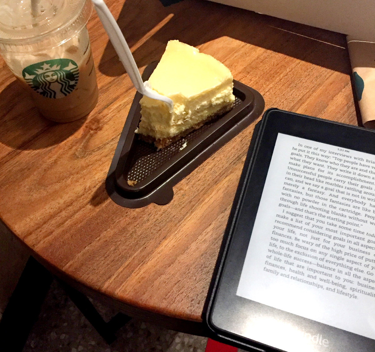 reading kindle in coffee shop while enjoy coffee and cheese cake