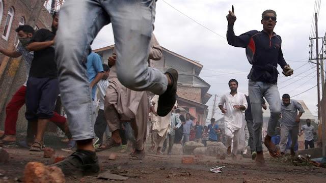ভারতীয় বাহিনীর টিয়ার গ্যাস থেকে আত্মরক্ষার জন্য দৌড়াচ্ছে কাশ্মীরিরা